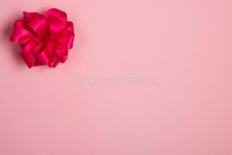 Το ανοιχτό ροζ σχεδόν κόκκινο, τόξο σατέν στην ανώτερη δευτερεύουσα γωνία ελαφριού αυξήθηκε ρόδινο υπόβαθρο υφάσματος με το δωμάτ στοκ φωτογραφίες με δικαίωμα ελεύθερης χρήσης