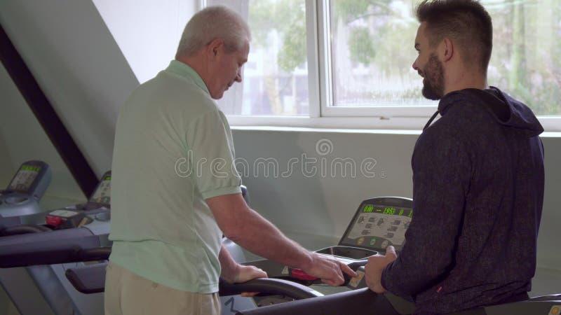 Το ανώτερο άτομο ανοίγει treadmill στοκ φωτογραφία