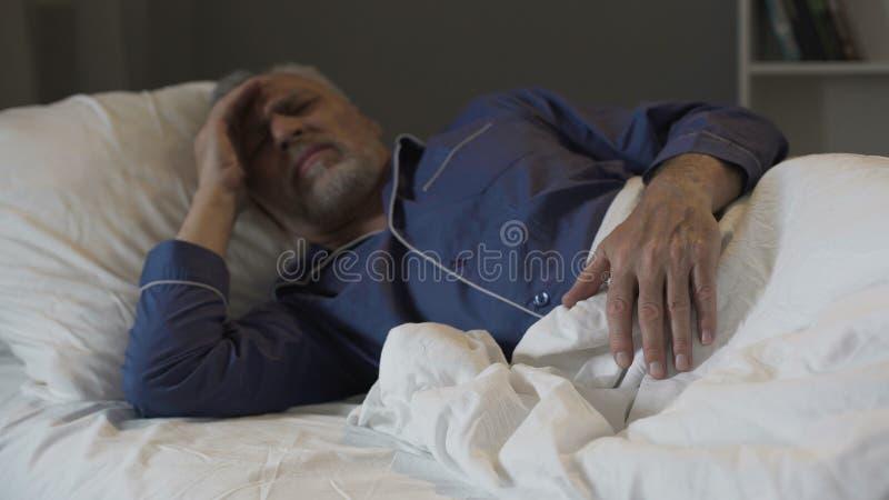 Το ανώτερο άτομο δεν μπορεί να κοιμηθεί, υφισμένος το φοβερούς πονοκέφαλο και την ημικρανία, αϋπνία στοκ εικόνα με δικαίωμα ελεύθερης χρήσης