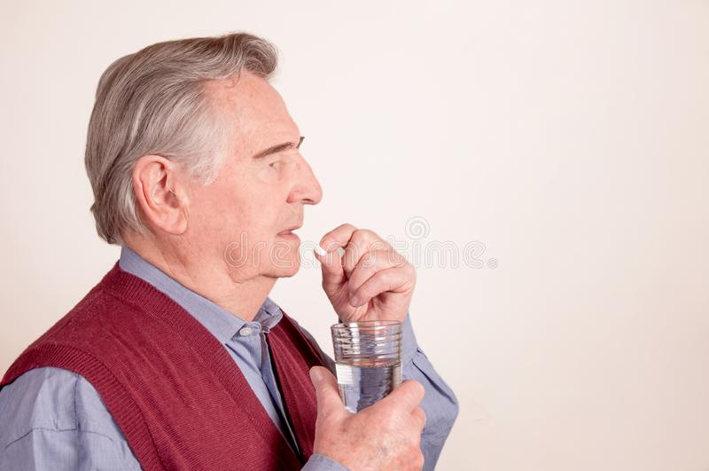 Το ανώτερο άτομο παίρνει το χάπι με το ποτήρι του νερού στοκ φωτογραφία