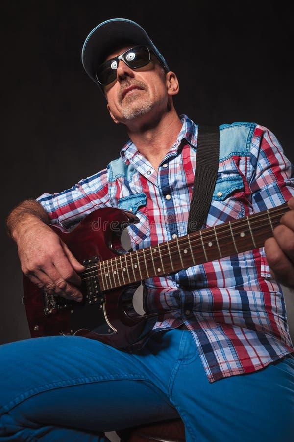 Το ανώτερο άτομο που παίζει μια ηλεκτρική κιθάρα που κάθεται, ανατρέχει στοκ φωτογραφία με δικαίωμα ελεύθερης χρήσης