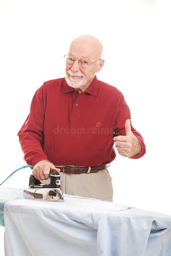 Το ανώτερο άτομο σιδερώνει το πουκάμισό του στοκ εικόνα