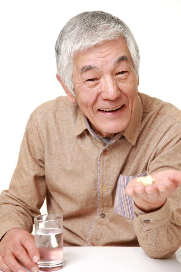 Το ανώτερο ιαπωνικό άτομο παίρνει ένα συμπλήρωμα στοκ εικόνα