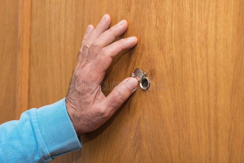 Το ανώτερο χέρι ατόμων ανοίγει την πόρτα κάλυψης ματάκι πόρτας στοκ φωτογραφίες με δικαίωμα ελεύθερης χρήσης