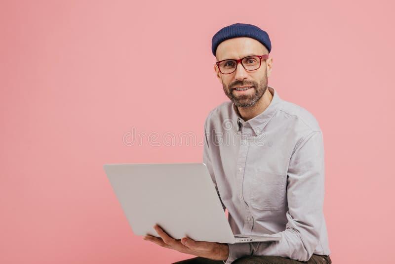 Το αξύριστο αρσενικό blogger ενημερώνει το σχεδιάγραμμά του, surfes κοινωνικά δίκτυα, αρχεία πολυμέσων μετοχών με τους οπαδούς, π στοκ εικόνες