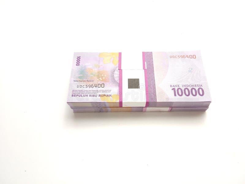 Το απλό επίπεδο φωτογραφιών βάζει, σωρός των χρημάτων της Ινδονησίας ρουπίων δέκα χιλιάδων δεσμών, στο άσπρο υπόβαθρο στοκ φωτογραφία