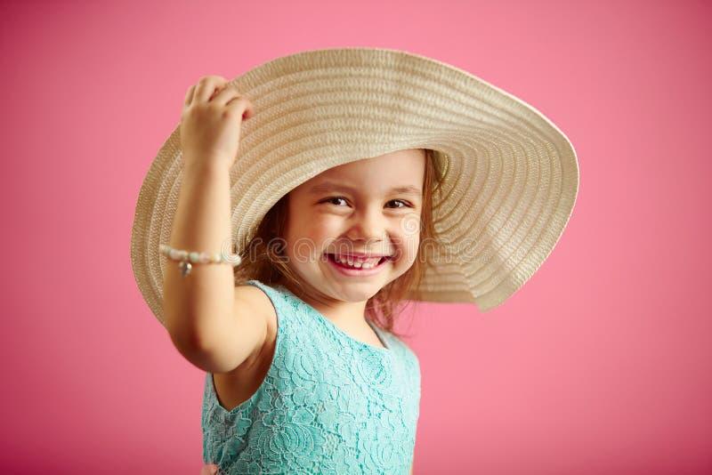 Το απομονωμένο πορτρέτο του μικρού κοριτσιού στο καπέλο του Παναμά, χαμόγελο, κρατά το καπέλο χεριών, στέκεται απομονωμένο στο ρο στοκ φωτογραφίες