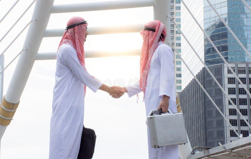 Το αραβικό τίναγμα επιχειρηματιών παραδίδει εξετάζει τη διαπραγμάτευση στην επιτυχία στοκ εικόνες