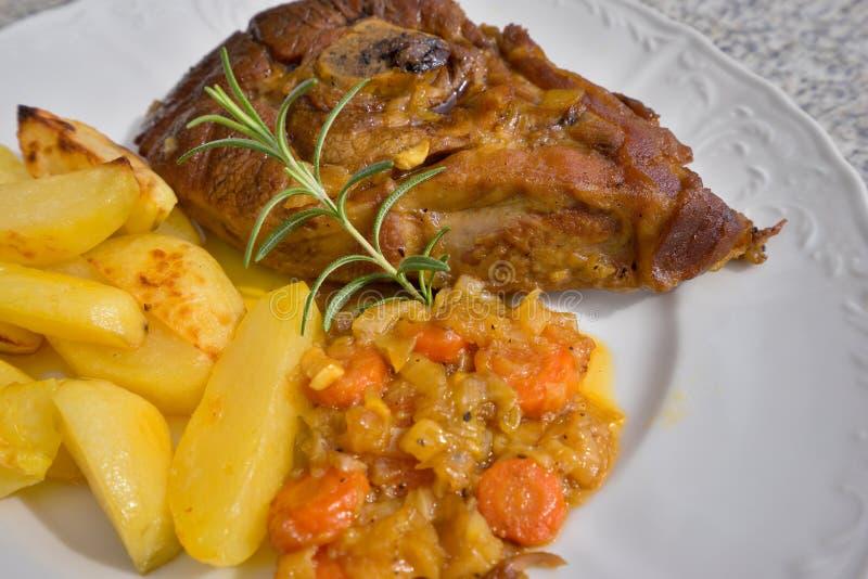 Το αργά ψημένο πόδι αρνιών άνοιξη με το δεντρολίβανο και το σκόρδο εξυπηρέτησε με τα γλυκά βερνικωμένα κρεμμύδια, καρότα, μήλα κα στοκ φωτογραφία με δικαίωμα ελεύθερης χρήσης