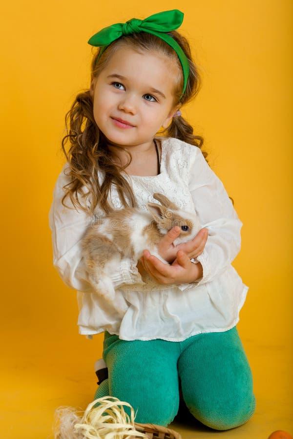 Το αρκετά ευτυχές κορίτσι παιδιών κρατά το φίλο της λίγο ζωηρόχρωμο κουνέλι, έννοια διακοπών Πάσχας που απομονώνεται σε κίτρινο στοκ φωτογραφία με δικαίωμα ελεύθερης χρήσης