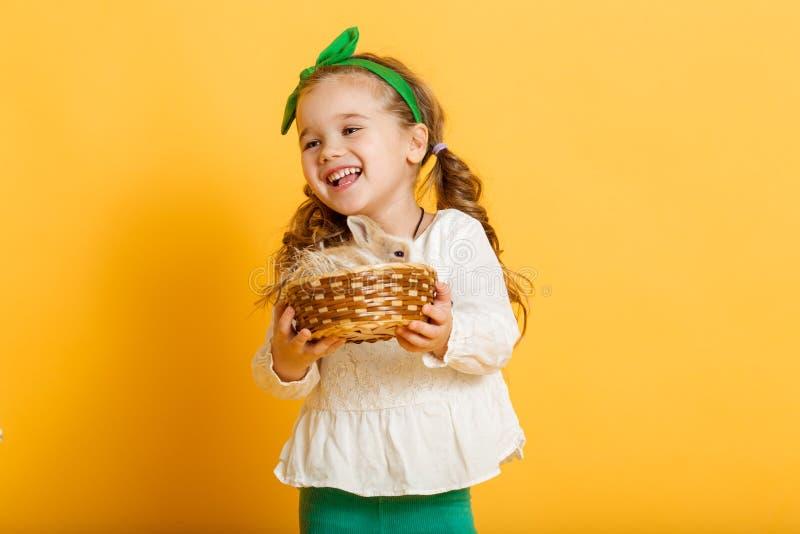 Το αρκετά ευτυχές κορίτσι παιδιών κρατά το φίλο της λίγο ζωηρόχρωμο κουνέλι, έννοια διακοπών Πάσχας που απομονώνεται σε κίτρινο στοκ εικόνα