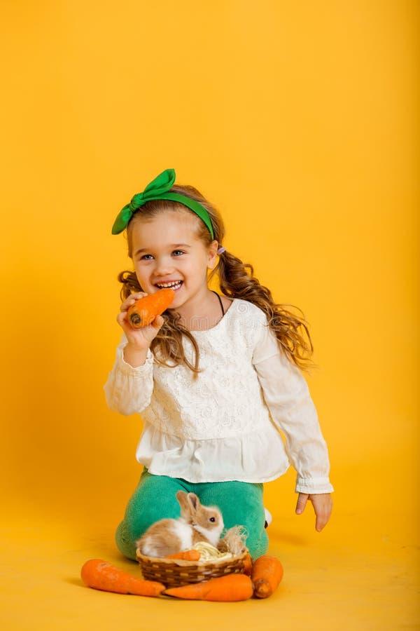 Το αρκετά ευτυχές κορίτσι παιδιών τρώει τα καρότα και το φίλο της λίγο ζωηρόχρωμο κουνέλι, έννοια διακοπών Πάσχας στοκ εικόνες με δικαίωμα ελεύθερης χρήσης