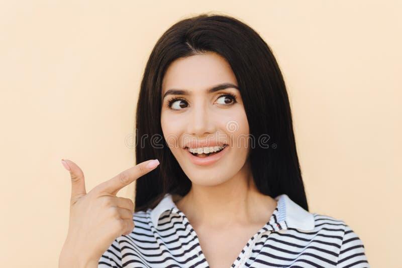 Το αρκετά νέο θηλυκό brunette με το υγιές δέρμα, δείχνει στα δόντια με τα στηρίγματα, φορά τη ριγωτή μπλούζα, κοιτάζει ευτυχώς κα στοκ φωτογραφίες