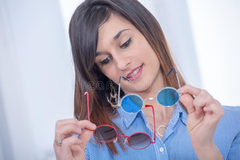 Το αρκετά νέο brunette επιλέγει ένα ζευγάρι των γυαλιών στοκ φωτογραφία με δικαίωμα ελεύθερης χρήσης