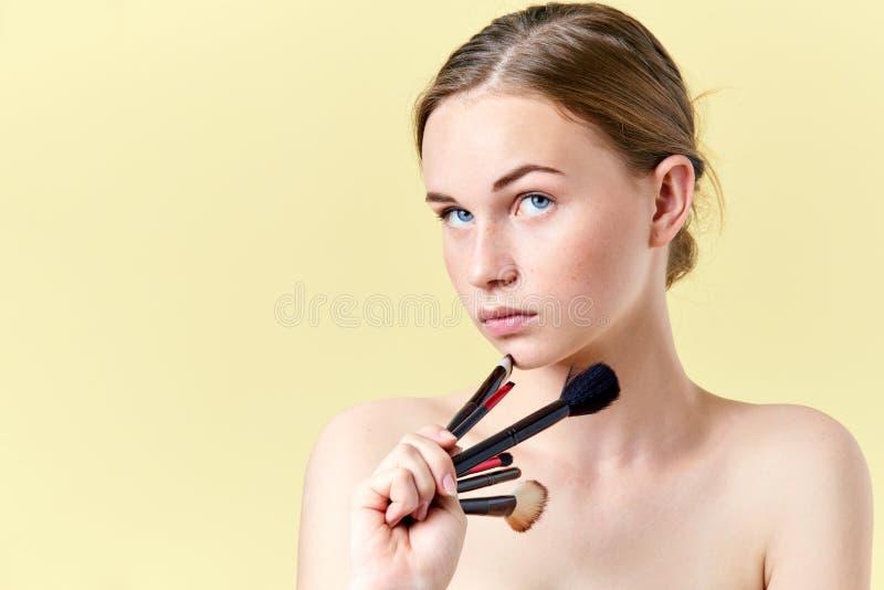 Το αρκετά redhead κορίτσι εφήβων με τα μπλε μάτια και τις φακίδες, που κοιτάζει μακρυά από τη κάμερα, που κρατά διαφορετικός αποτ στοκ φωτογραφία με δικαίωμα ελεύθερης χρήσης