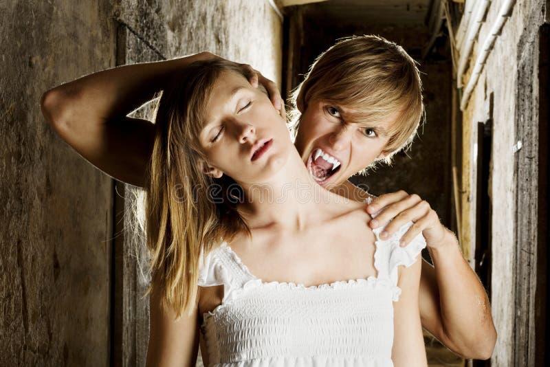 Το αρσενικό βαμπίρ θέλει να δαγκώσει μια ξανθή γυναίκα στοκ φωτογραφίες