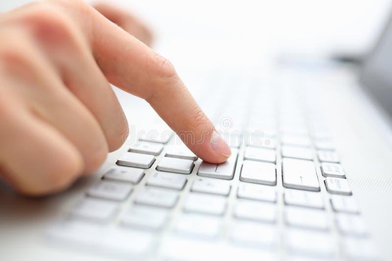 Το αρσενικό δάχτυλο χεριών πιέζει εισάγει το κλειδί στο πληκτρολόγιο lap-top στοκ εικόνες