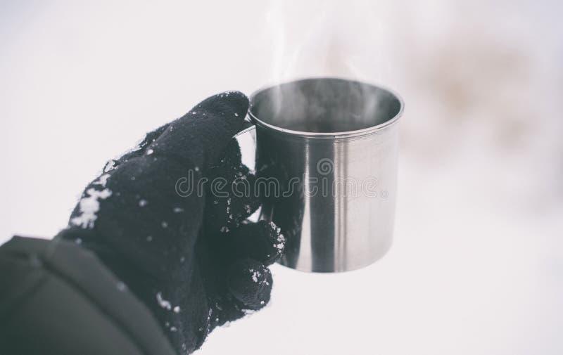 Το αρσενικό παραδίδει τα γάντια κρατώντας το φλυτζάνι με το καυτό τσάι ή τον καφέ Σπάσιμο τσαγιού Έννοια χειμώνα στοκ φωτογραφίες