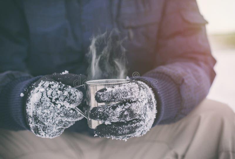 Το αρσενικό παραδίδει τα γάντια κρατώντας το φλυτζάνι με το καυτό τσάι ή τον καφέ Σπάσιμο τσαγιού Έννοια χειμώνα στοκ φωτογραφία