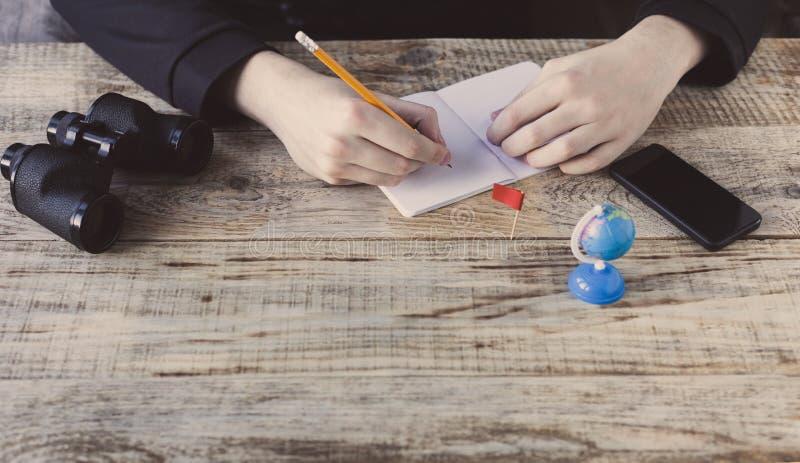 Το αρσενικό παραδίδει το υπόβαθρο καφέδων - παρουσιάστε τις ξύλινες σανίδες, smartphone, nootbook, μολύβι, σφαίρα, διόπτρες, σημα στοκ εικόνες