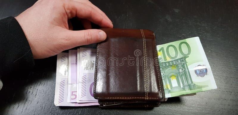 Το αρσενικό χέρι αγγίζει ένα καφετί σύνολο πορτοφολιών δέρματος με τα ευρο- τραπεζογραμμάτια στοκ εικόνα