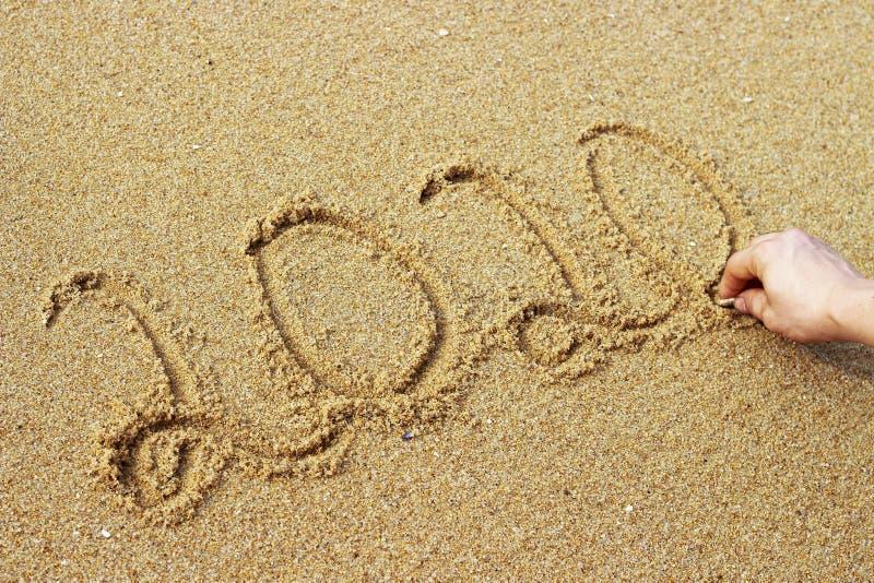 Το αρσενικό χέρι επισύρει την προσοχή στο έτος άμμου το 2020, τοπ άποψη στοκ φωτογραφίες με δικαίωμα ελεύθερης χρήσης