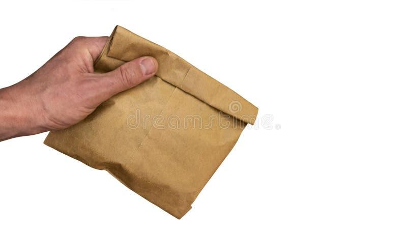 Το αρσενικό χέρι κρατά μια τσάντα καφετιού εγγράφου με το περιεχόμενο η ανασκόπηση απομόνωσε το λευκό διάστημα αντιγράφων Το θέμα στοκ εικόνες με δικαίωμα ελεύθερης χρήσης