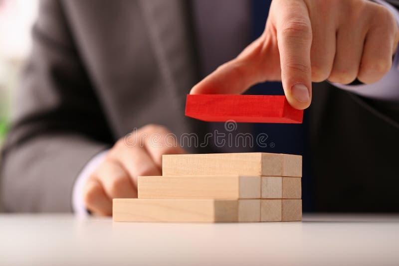 Το αρσενικό χέρι κρατά τον κόκκινο ξύλινο φραγμό του σκαλοπατιού στοκ εικόνες με δικαίωμα ελεύθερης χρήσης