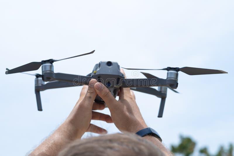 Το αρσενικό χέρι προωθεί τον κηφήνα για την πτήση, με την οποία μπορείτε να πάρετε τις φωτογραφίες και την τηλεοπτική μαγνητοσκόπ στοκ εικόνες