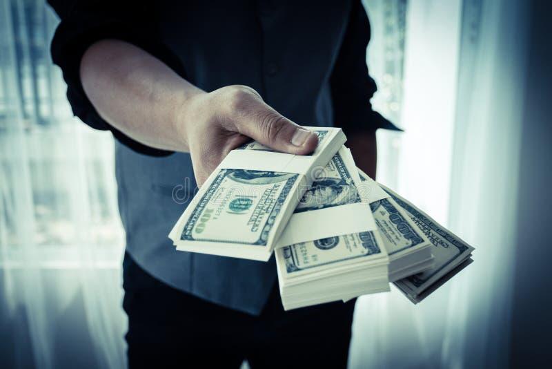 Το αρσενικό χέρι στέλνει πολλά χρήματα μπροστινά στοκ εικόνα