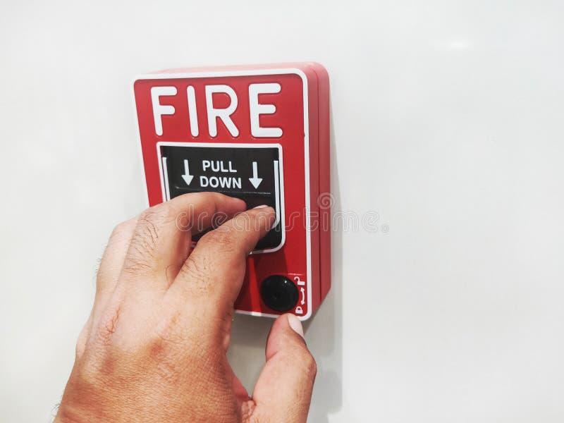Το αρσενικό χέρι ωθεί το συναγερμό πυρκαγιάς στοκ εικόνες