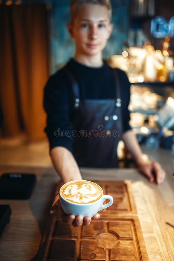 Το αρσενικό barista παρουσιάζει φλιτζάνι του καφέ με το σχέδιο αφρού στοκ φωτογραφία με δικαίωμα ελεύθερης χρήσης