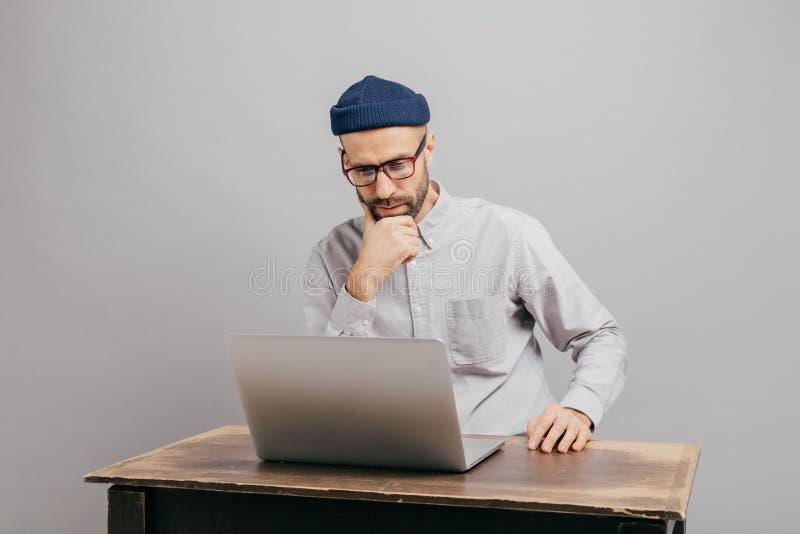 Το αρσενικό freelancer διαβάζει τις ειδήσεις σε Διαδίκτυο, εξετάζει προσεκτικά το φορητό προσωπικό υπολογιστή, προσέχει το βίντεο στοκ εικόνες