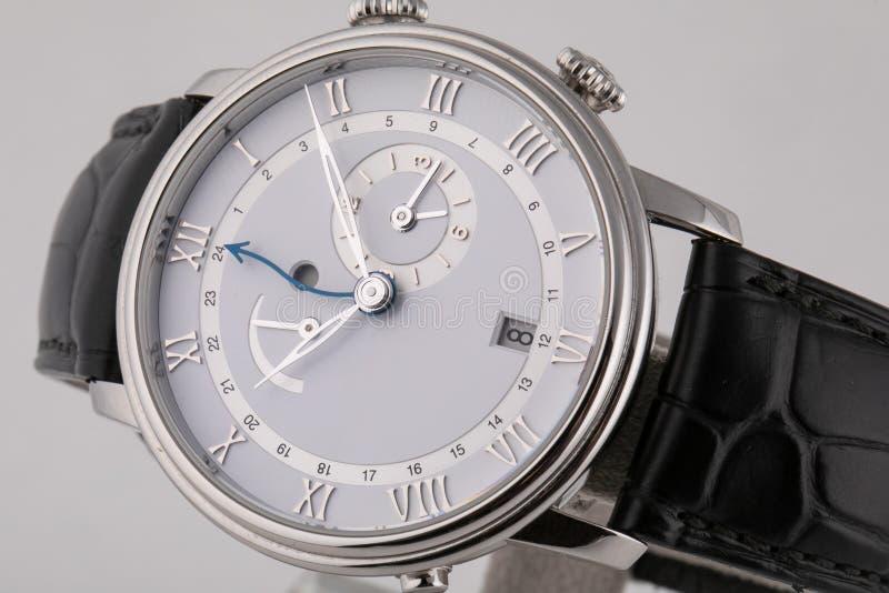 Το ασημένιο wristwatch με τον άσπρο πίνακα, το ασήμι δεξιόστροφα, το χρονόμετρο με διακόπτη και chronograph στο μαύρο δέρμα δένου στοκ φωτογραφίες