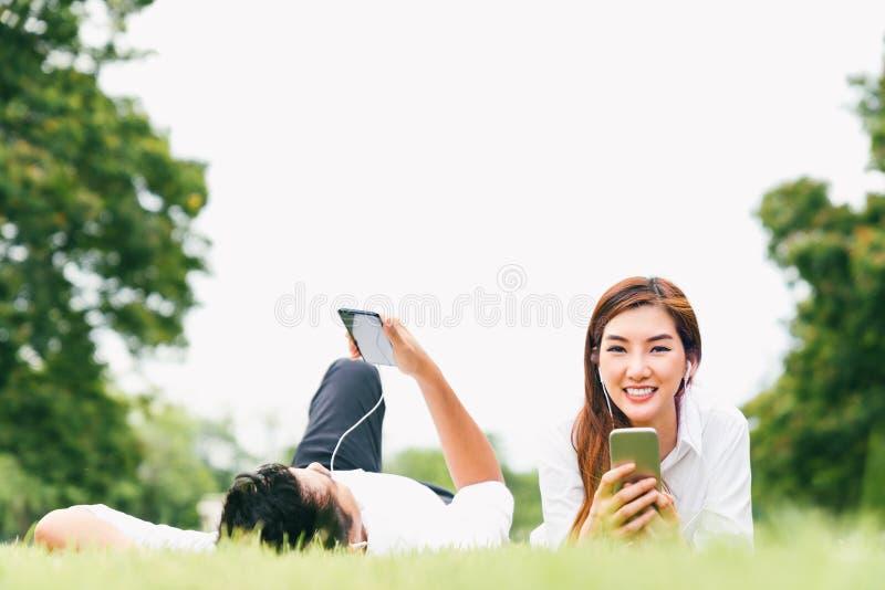 Το ασιατικός ζεύγος ή ο φοιτητής πανεπιστημίου εραστών που χρησιμοποιεί το κινητό τηλέφωνο ακούει τη μουσική μαζί δημόσια σταθμεύ στοκ εικόνα