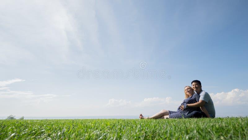 Το ασιατικό άτομο με μια έγκυο γυναίκα στηρίζεται στη φύση σε μια γραφική θέση, κάθεται στην πράσινη χλόη στοκ φωτογραφία