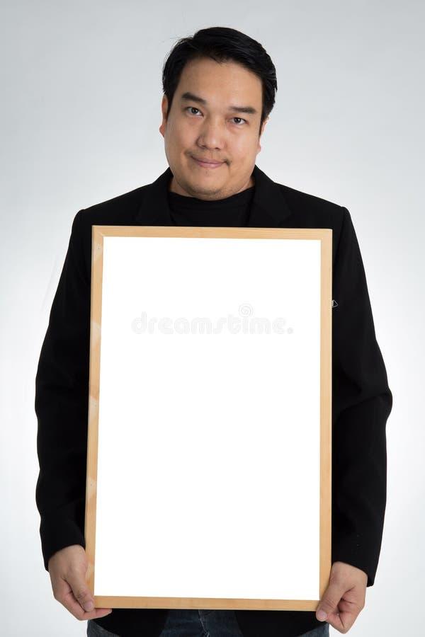 Το ασιατικό άτομο στο μαύρο κοστούμι κρατά έναν κενό λευκό πίνακα στοκ εικόνες