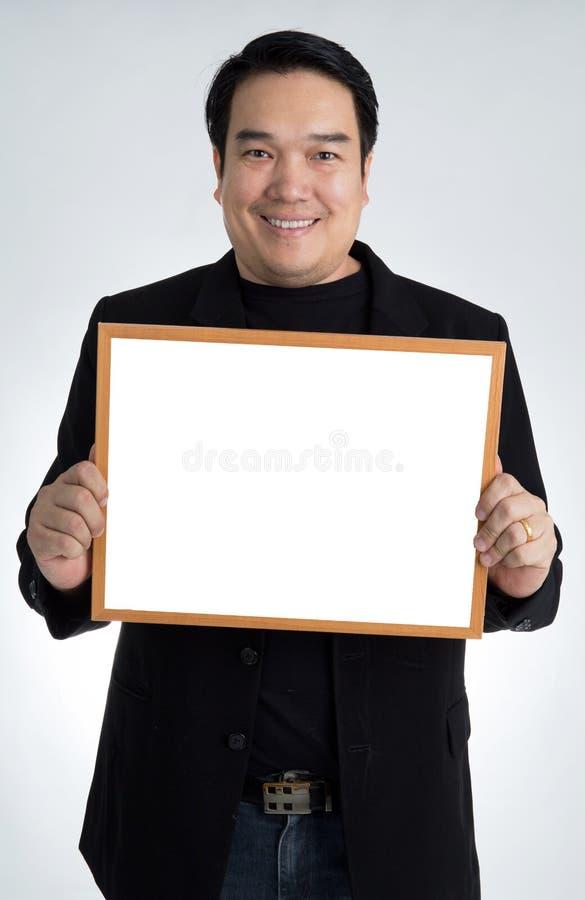Το ασιατικό άτομο στο μαύρο κοστούμι κρατά έναν κενό λευκό πίνακα στοκ φωτογραφίες
