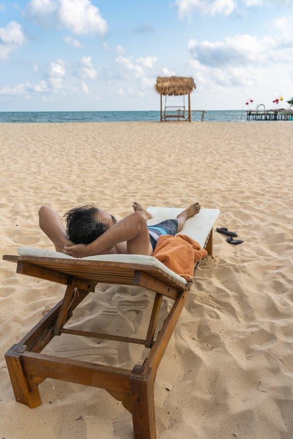Το ασιατικό άτομο χαλαρώνει στην παραλία στο θέρετρο στοκ εικόνες