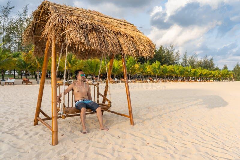 Το ασιατικό άτομο χαλαρώνει στην ταλάντευση στην παραλία στοκ φωτογραφία με δικαίωμα ελεύθερης χρήσης