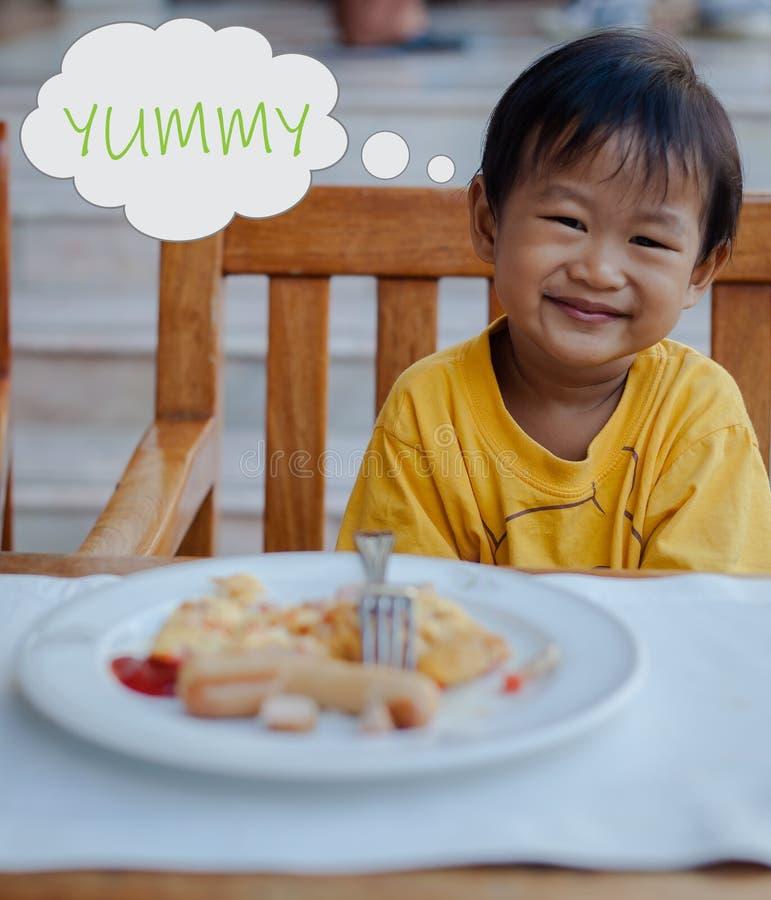 Το ασιατικό αγόρι απολαμβάνει το πρόγευμά του στοκ εικόνα