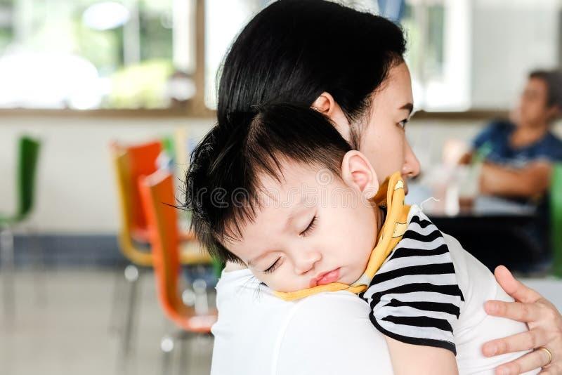 Το ασιατικό αγόρι πέφτει κοιμισμένο στη μητέρα του στοκ φωτογραφίες