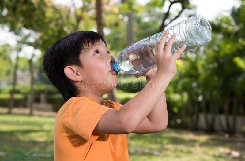 Το ασιατικό αγόρι πίνει το νερό στοκ εικόνες με δικαίωμα ελεύθερης χρήσης