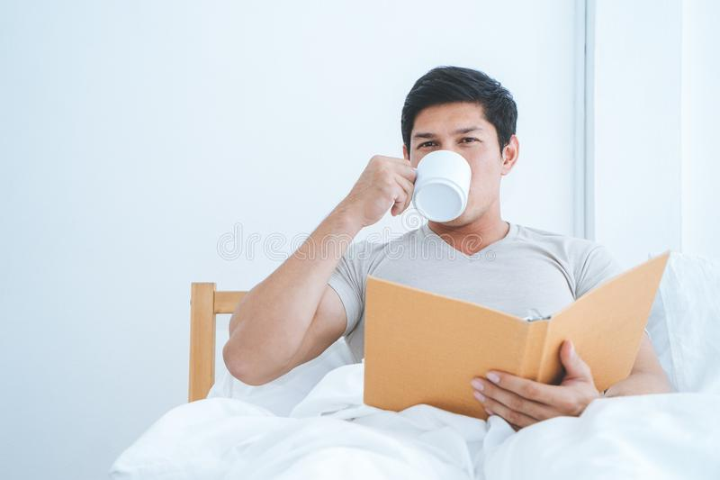 Το ασιατικό αρσενικό βιβλίο ανάγνωσης και πίνει τον καφέ στο κρεβάτι πρωινού στοκ φωτογραφίες