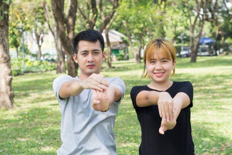 Το ασιατικό γλυκό ζεύγος θερμαίνει τους οργανισμούς τους με το τέντωμα των όπλων πριν από τη jogging άσκηση πρωινού στο πάρκο στοκ εικόνα