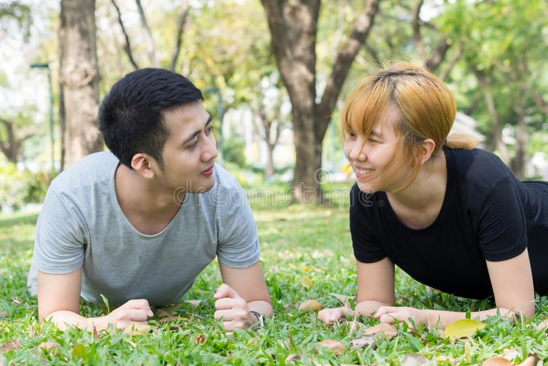 Το ασιατικό γλυκό ζεύγος που ασκεί μαζί με το χαμόγελο στα πρόσωπά τους στη μαλακή χλόη περικυκλώνει με τη φύση στοκ φωτογραφία με δικαίωμα ελεύθερης χρήσης