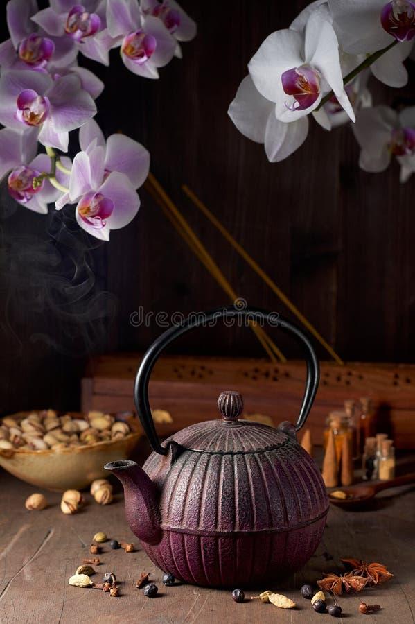 Το ασιατικό δοχείο τσαγιού χυτοσιδήρου, φυστίκια, ορχιδέα ανθίζει και διακοσμητικά καρυκεύματα στοκ εικόνες με δικαίωμα ελεύθερης χρήσης