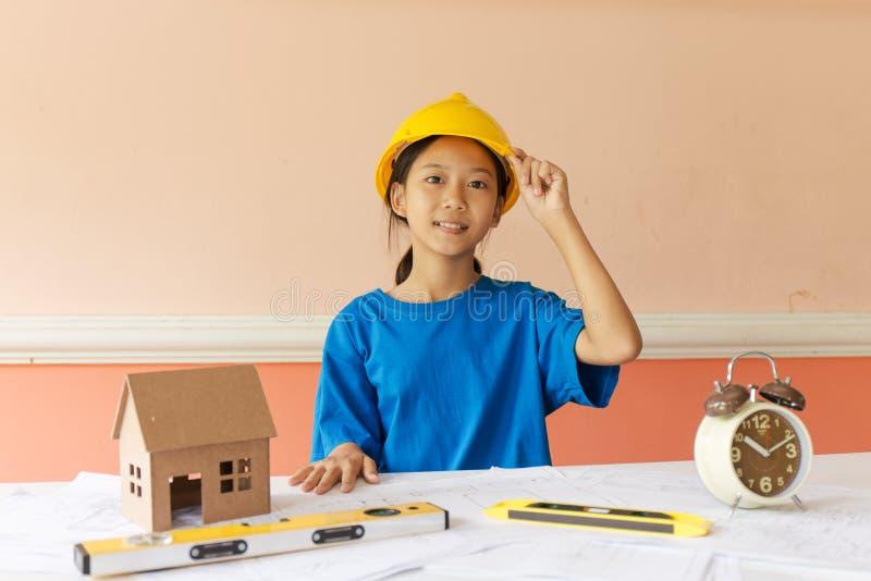 Το ασιατικό κορίτσι έχει τη φιλοδοξία να είναι δομικός μηχανικός με ένα κράνος και το σχέδιο οικοδόμησης που τίθεται στον πίνακα στοκ εικόνες