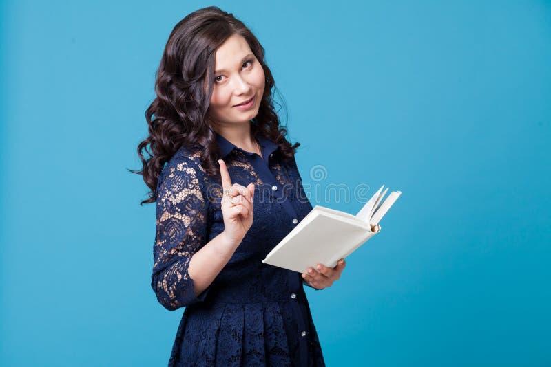 Το ασιατικό κορίτσι κρατά ένα βιβλίο και παρουσιάζει δάχτυλό της στοκ φωτογραφίες