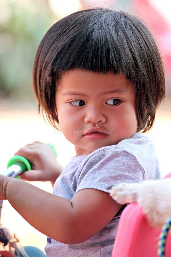Το ασιατικό κορίτσι παιδιών μωρών κοιτάζει επίμονα σε κάτι. στοκ φωτογραφίες